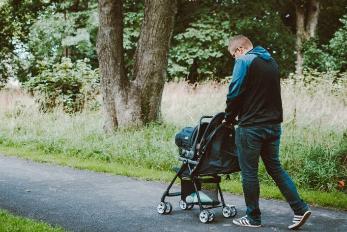 a man pushing a baby pram