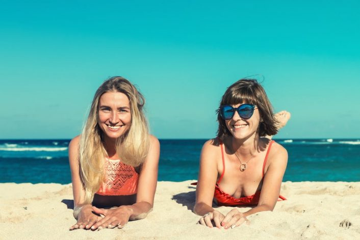 two women lying on the beach sand wearing their designer bathing suits